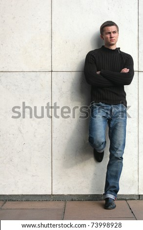 Young sexy man leaning in the marble background