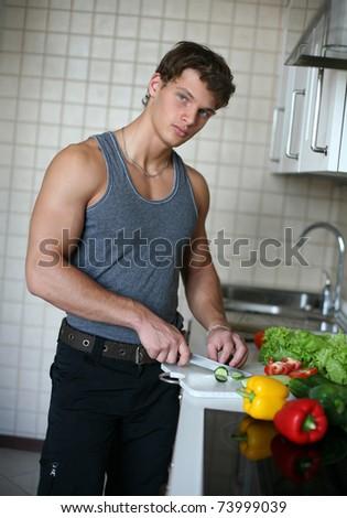 Young sexy man preparing salad at the kitchen - stock photo