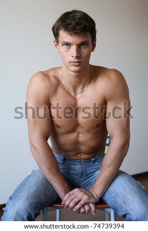 Young sexy man sitting on a chair - stock photo