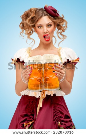 Young sexy Oktoberfest waitress, wearing a traditional Bavarian dress dirndl, serving two big beer mugs in a tavern and licking her lips on blue background. - stock photo