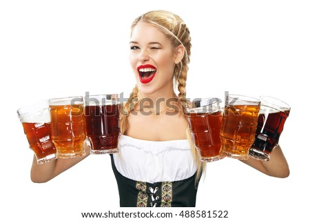 Young sexy Oktoberfest waitress, wearing a traditional Bavarian dress, serving big beer mugs isolated on white background.