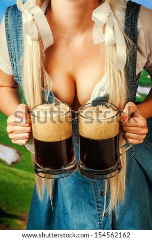 young sexy oktoberfest woman wearing a dirndl holding two dark beer mugs