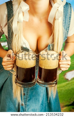 young sexy oktoberfest woman wearing a dirndl holding two dark beer mugs - stock photo