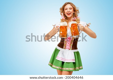 Young sexy Oktoberfest woman wearing a traditional Bavarian dress dirndl serving two beer mugs with happy smile on blue background.