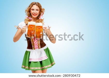 Young sexy Oktoberfest woman wearing a traditional Bavarian dress dirndl serving two beer mugs with happy smile on blue background. - stock photo
