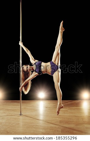 Young sexy pole dance woman doing splits - stock photo