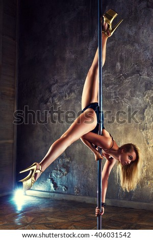 Young sexy pole dance woman on old wall background - stock photo