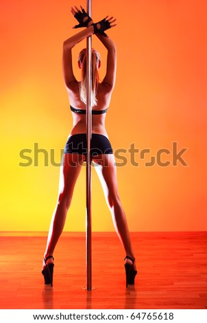 Young sexy pole dance woman. Vibrant red light. - stock photo