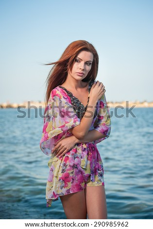 Young sexy red hair girl in multicolored blouse posing on the beach. Sensual attractive woman with long hair, summer shot at sea shore. Perfect body female, holiday concept turquoise water background - stock photo
