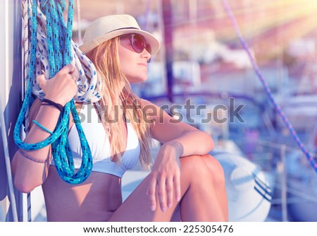 Young sexy sailor girl relaxing on sailboat, holding rope, enjoying sea cruise, active lifestyle, female in mild sunset light, summer vacation concept - stock photo