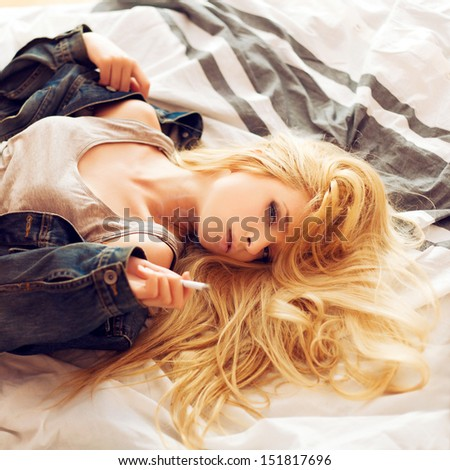 Young sexy sensual blond woman lying on the bed and smoking cigarette.  - stock photo