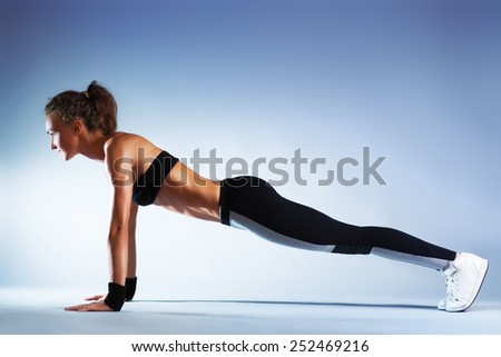 Young sexy slim brunette fitness woman doing push-ups on blue wall background. - stock photo