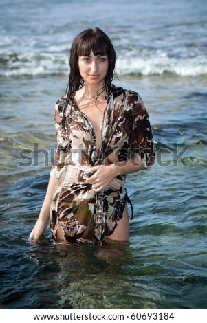 Young sexy slim brunette woman in a wet beach dress standing in ocean water. Tenerife, Spain. - stock photo