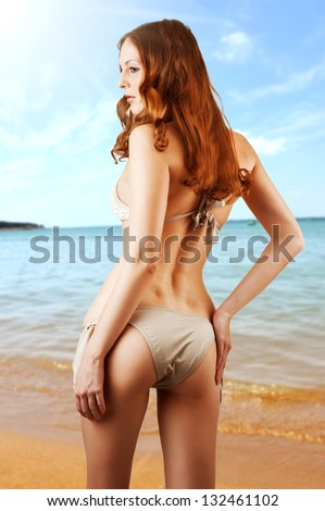 Young sexy slim woman in beige bikini on a beach - stock photo
