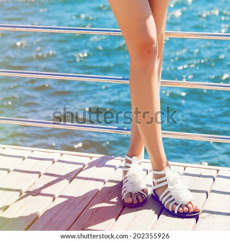 Young sexy slim woman posing at wood pier near blue sea shearing white floral sandals, Bright colors vacation mood. - stock photo