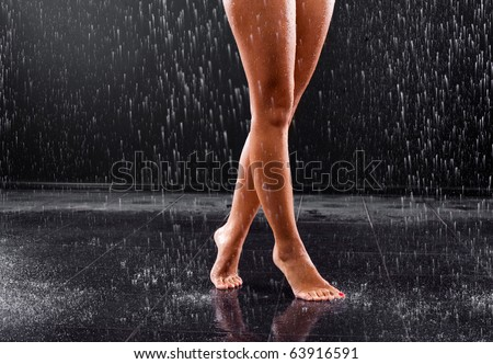 young sexy slim woman taking a shower and standing on the tiled floor - stock photo