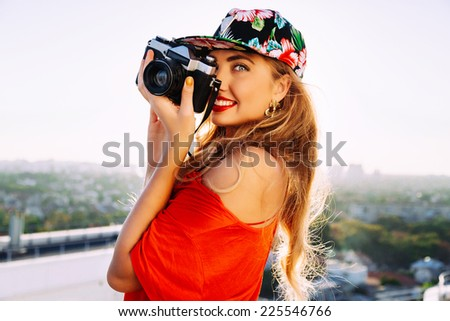 Young sexy smiling photographer woman, holding and making picture on retro vintage camera, wearing swag floral bright cap, amazing view on the city from roof, joy and happiness. - stock photo