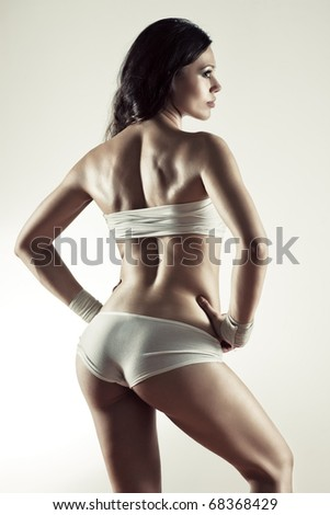 Young sexy sporty woman. Soft yellow tint. - stock photo