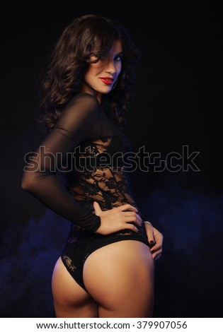 young sexy striptease dancer over dark background - stock photo