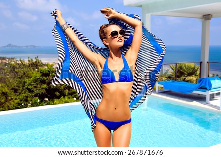 Young sexy stunning woman having fun at pool party on luxury villa, enjoy her summer vacation, wearing bikini sunglasses and color matching scarf, amazing view on tropical island ocean. - stock photo