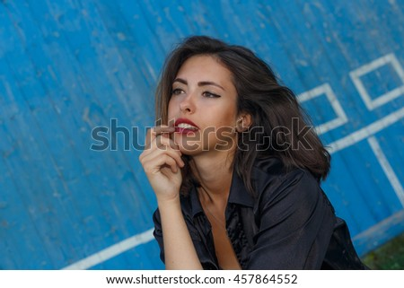 Young sexy suntanned woman in a short top and shirt with beautiful modern make-up and hair posing against blue painted wooden wall, portrait with copy space, horizontal view - stock photo
