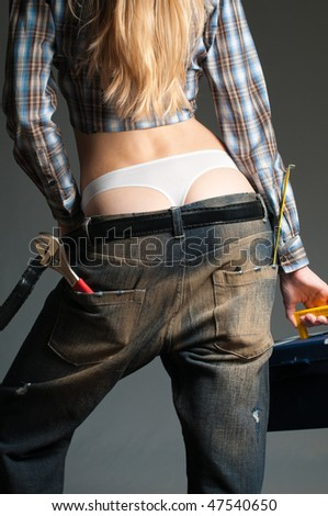 young sexy woman against dark background wearing lowered oversized jeans with pockets full with tools - stock photo
