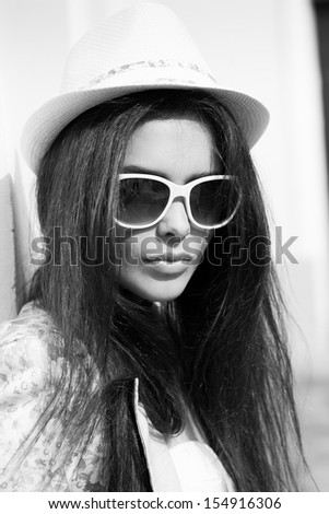 Young sexy woman closeup portrait. Stylish woman posing on the street with interested look and hat on her head. - stock photo