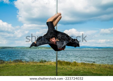 Young sexy woman exercise pole dance - stock photo