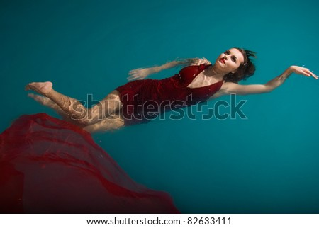 Young sexy woman floating on swimming pool in red dress. beauty shot - stock photo