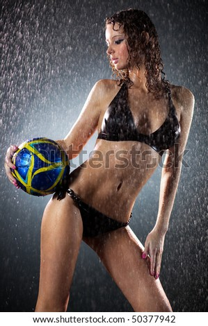 Young sexy woman football player. Water studio photo. - stock photo