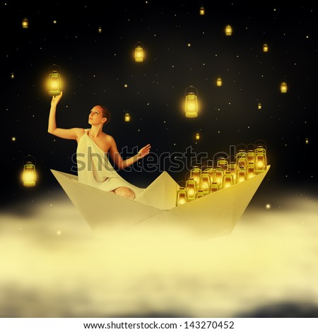 Young sexy woman goddess floating on clouds in a paper boat and hanging stars in night sky - stock photo