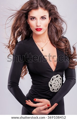 Young sexy woman in black dress posing at studio on white background. Gorgeous brunette with long hair. fashionable style. - stock photo
