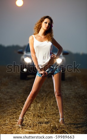 Young sexy woman in car headlights. - stock photo