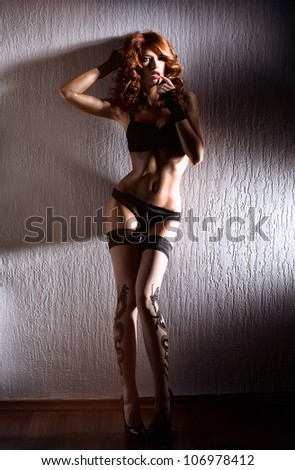 Young sexy woman in erotic lingerie standing near the grey wall