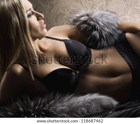Young sexy woman in lingerie posing over vintage background - stock photo