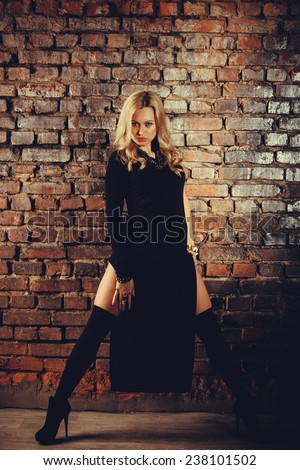 Young sexy woman in long black dress on brick wall background. Warm colors. - stock photo