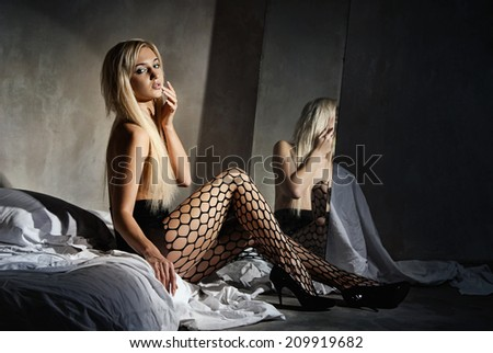 Young sexy woman in pantyhose on a bed in front of a mirror in a dark room - stock photo