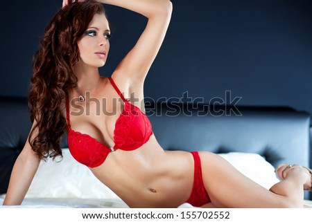 Young sexy woman in red lingerie portrait. - stock photo
