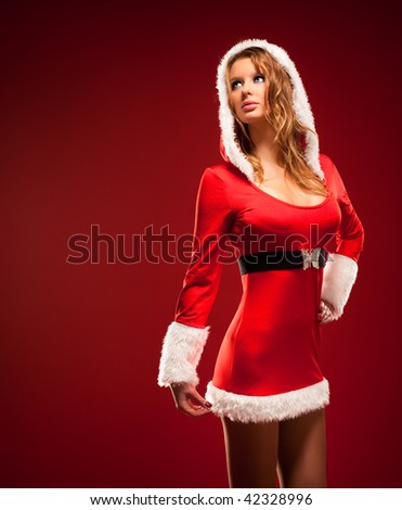 Young sexy woman in santa clothing. On red background. - stock photo
