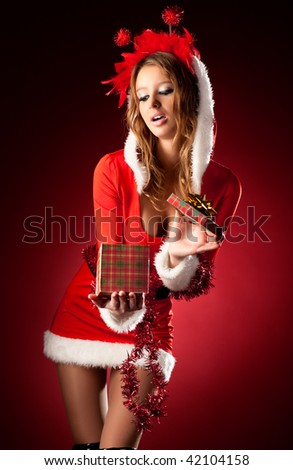Young sexy woman in santa clothing. Opening a gift box. - stock photo