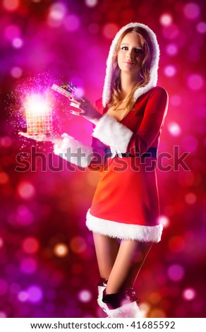 Young sexy woman in santa clothing opening magic box. - stock photo