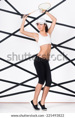 Young sexy woman in sportswear posing with badminton racket - stock photo