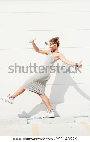 Young sexy woman in sunglasses. Outdoor lifestyle portrait of girl in grey dress