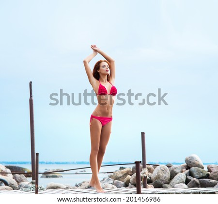 Young sexy woman in swimsuit relaxing on the pier - stock photo