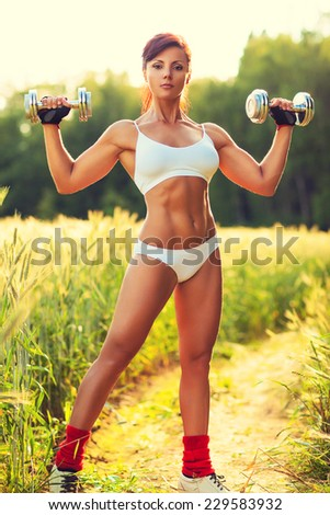 Young sexy woman in white clothing sports training at summer field. Chrome heavy dumbbells in hands. Res sunset light. - stock photo