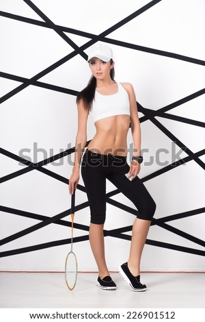 Young sexy woman in white top and black leggings posing with badminton racket - stock photo