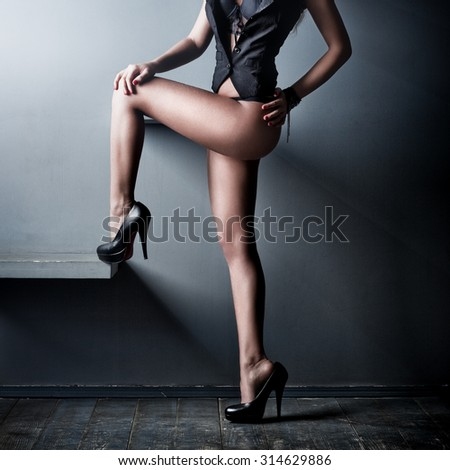 Young sexy woman legs on wall background. - stock photo