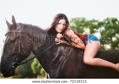Young sexy woman lie on horse - stock photo