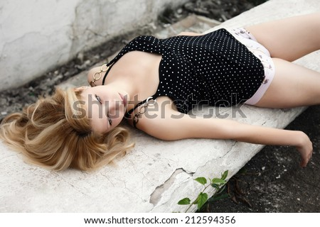 Young sexy woman lying on the stone bench - stock photo