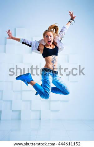 Young sexy woman modern dancer with tattoo on body jumping in bright white interior - stock photo